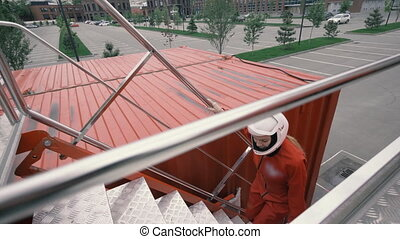 Girl in red overalls and protective helmet rises up stairs