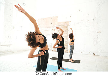Group of young women doing yoga stretching exercises