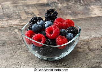 Healthy berries in crystal bowl on wooden table