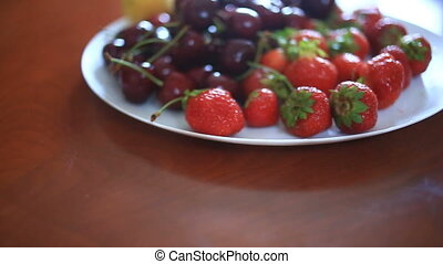 Dish with cherries and strawberries close-up.