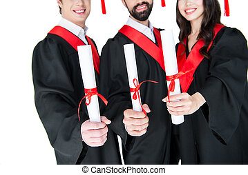 Cropped shot of smiling students in graduation gowns holding diplomas on white