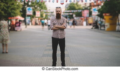 Zoom in timelapse of Young bearded man standing still at sidewalk in crowd traffic with people moving fast