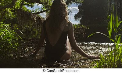 Young woman sitting in a river in shallow water - Rear view...