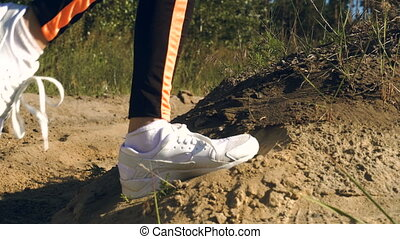 female in white sneakers working out outdoors - close up...