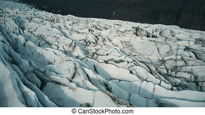 Copter fly over the ice ridge in Iceland. Close-up aerial view of white glacier Vatnajokull with black ash.