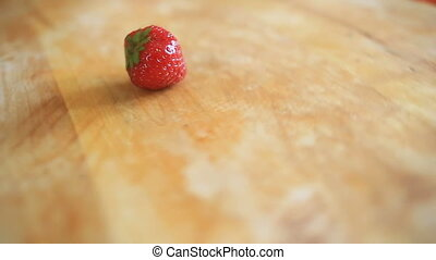 One strawberry berry lies on a wooden board that rotates around its axis