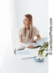 Young woman sitting indoors reading book - Photo of young...