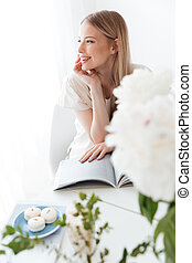 Happy woman sitting indoors reading book - Image of young...