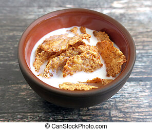 Wheat bran breakfast cereal with milk in clay bowl