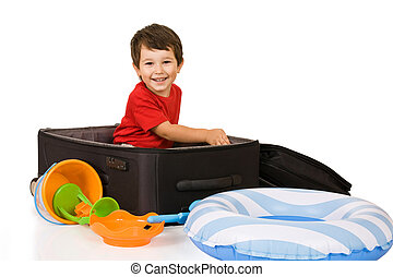 Little boy packs a suitcase