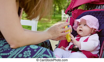 Woman with Pram Sitting on the Bench in the Park - Woman...