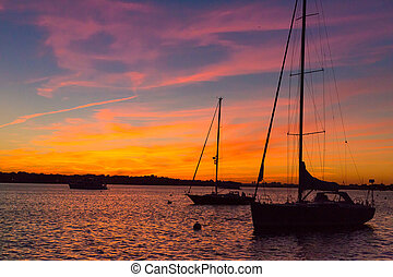 Epic and beautiful sunset over harbor with sailboat silouettes