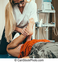 Physical therapist working with male patient