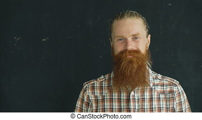 Closeup portrait of hipster man looking at camera and smiling on black background