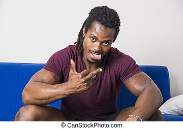 Black man sticking out tongue and doing gesture - Happy...