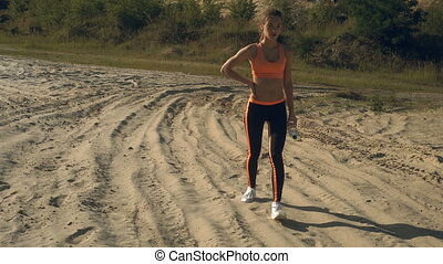 sports lady after workout walks with water in bottle in her...