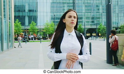Young woman in a hurry late for work looking at watches...