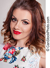 Beautiful Brown-haired model girl on white background . Hairstyle pigtail . Red lips and nails manicure
