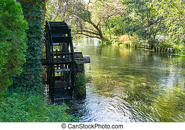 Water mill wheel on river. Water power and renewable energy...
