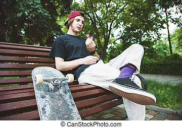 Long-haired hipster skater in a cap sits on a bench and...