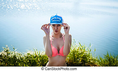 Young sexy woman in swimsuit in snapback on her head,...