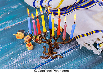 The Jewish menorah with candles, sweet donuts, and dreidel...