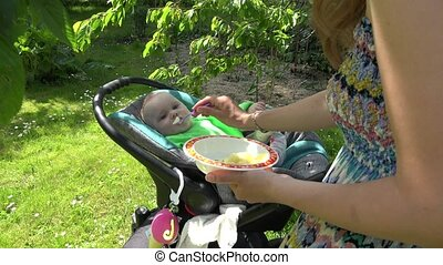 mother feed baby in chariot outdoor. Motherhood and...