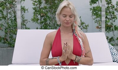 Attractive girl in the red bathing suit practicing yoga...