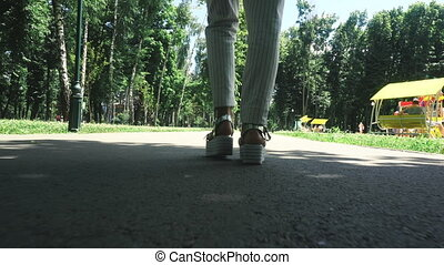 elegant woman on high heels walks at the park - cose up of...