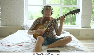 Attractive bearded man sitting on bed learning to play...