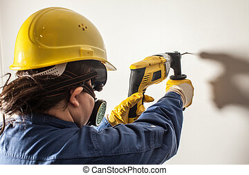 Female worker drills the wall, hard work for women