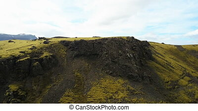 Aerial view of the green lava field with bumps covered moss....