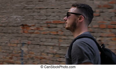 A young man is walking in front of a brick wall