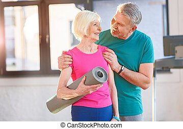 Happy old couple with yoga mat in fitness class