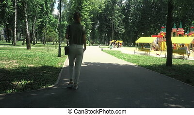 young blonde lady walks at the park on high heels at warm...