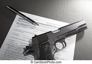 Handgun transfer paperwork - Pen and handgun with paperwork...