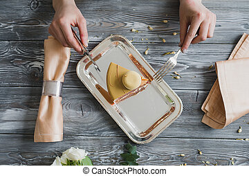 Top view of hands going to eat dessert, yellow mousse cake...