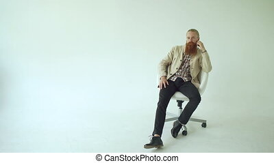 Serious bearded man sitting on swivel office chair and looking into camera on white background