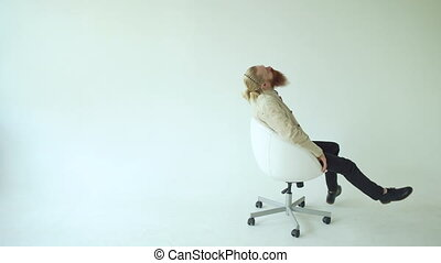 Boring bearded man turning on swivel office chair on white...