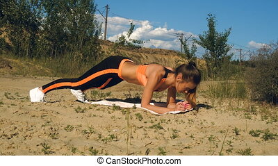 attractive blonde lade makes sports exercices on a sand