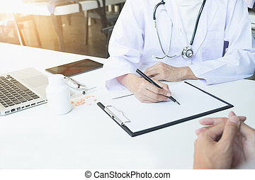 Health care and Medical concept, patient listening intently to a female doctor explaining patient symptoms or asking a question as they discuss paperwork together in a consultation