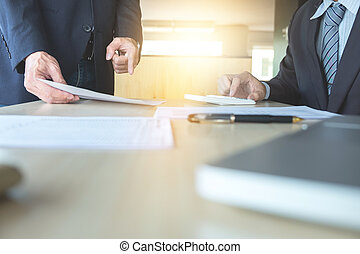 Businessman analysis on calculator, new plan financial graph data with business colleagues pointing at paperwork in the office