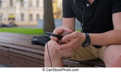 Young man talking on mobile phone on a bench in the city