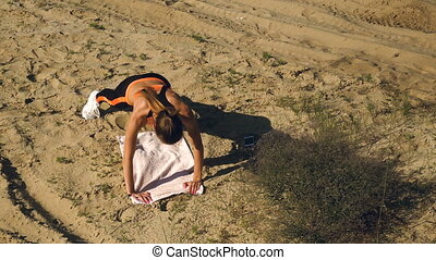 slim sports lady makes exercices for abs muscles on a sand...