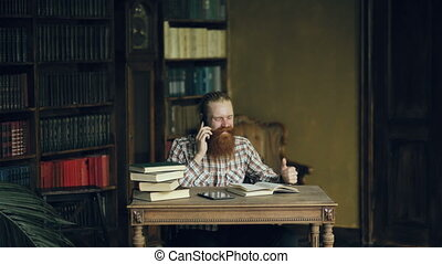 Young bearded student talking phone while preparing for exams in univercity library