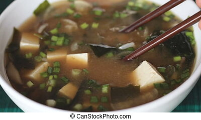Picking up miso soup ingredients with chopsticks - Macro...