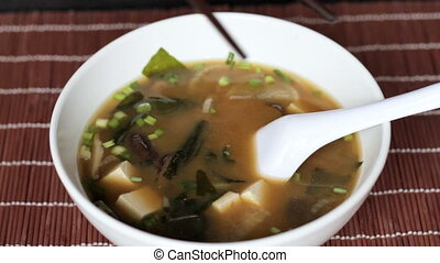 Tofu and mushrooms spooned out from miso soup - Female hands...