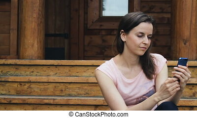 Attractive girl types text on her mobile outdoors