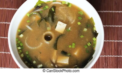 View from above on bowl of miso soup eaten with chopsticks...