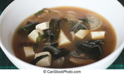 Filling white bowl with miso soup - Extreme close up of...